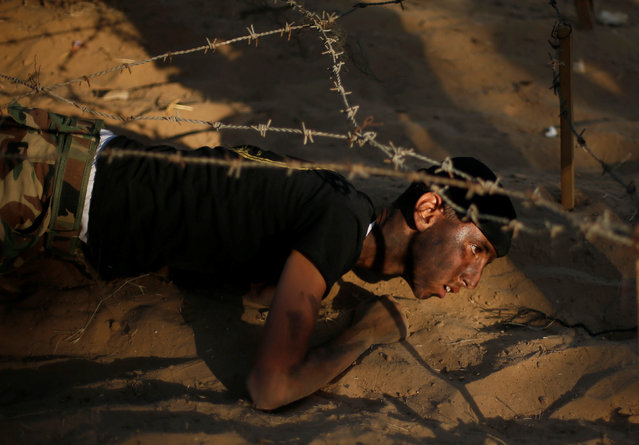 A young Palestinian crawls under barbed wire as he takes part in a military-style graduation ceremony at a summer camp organized by the Islamic Jihad Movement in Khan Younis in the southern Gaza Strip July 15, 2016. (Photo by Suhaib Salem/Reuters)