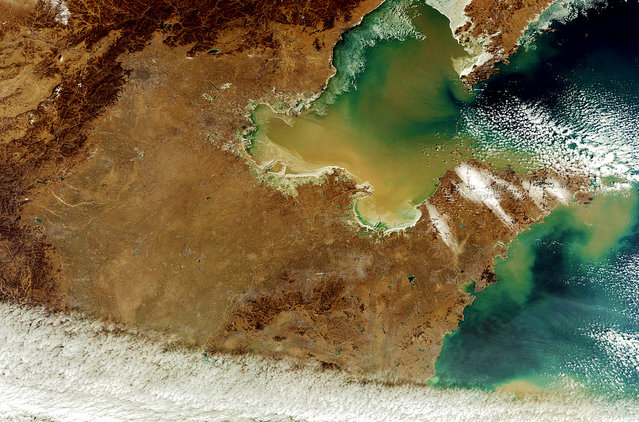This photo of Northern China shows the Yellow River flowing into the Yellow Sea. Beijing and Tanjing are shaded circles in the top-center part of the photo. (Photo by The European Space Agency)
