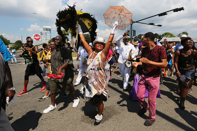 Revelers march in the Lower Ninth Ward during a second line parade marking the 10th anniversary of Hurricane Katrina on August 29, 2015 in New Orleans, Louisiana. (Photo by Mario Tama/Getty Images)