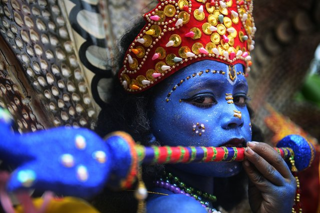 A Bangladeshi youth dressed as the Hindu god Lord Krishna takes part in a procession during celebrations for the Janmashtami festival in Dhaka on August 17, 2014. The Hindu festival of Janmashtami which falls on August 17 in 2014 marks the birth of the Hindu god Lord Krishna. (Photo by Munir Uz Zaman/AFP Photo)