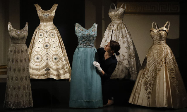 A woman adjusts evening dresses of Britain's Queen Elizabeth at an exhibition at Buckingham Palace in London, Thursday, July 21, 2016. (Photo by Frank Augstein/AP Photo)