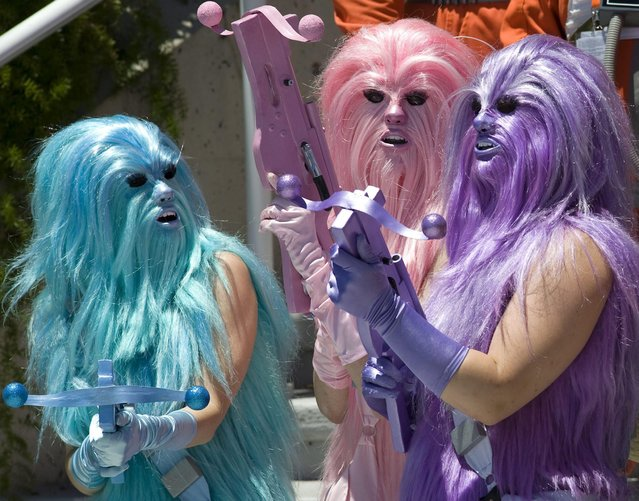 Convention goers dressed as bright colored Wookiees, a fictional species from the US epic space opera franchise Star Wars, prepare for a group photo outside the Comic Con 2016 in San Diego, California, USA, 22 July 2016. The San Diego Comic Con 2016 runs from 21 until 24 July. (Photo by David Maung/EPA)
