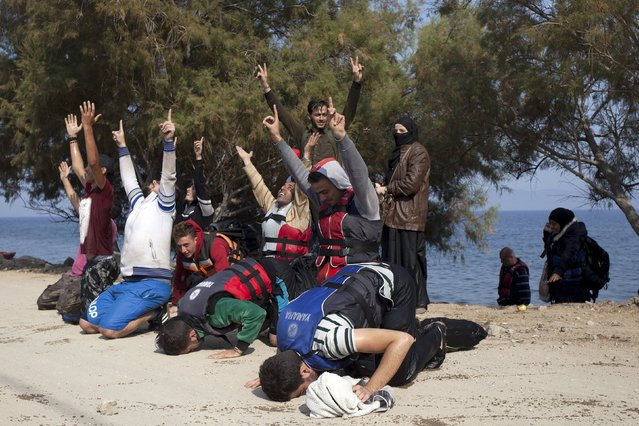 Syrian refugees raise their hands to the sky while praying, moments after arriving on the Greek island of Lesbos September 3, 2015. (Photo by Dimitris Michalakis/Reuters)