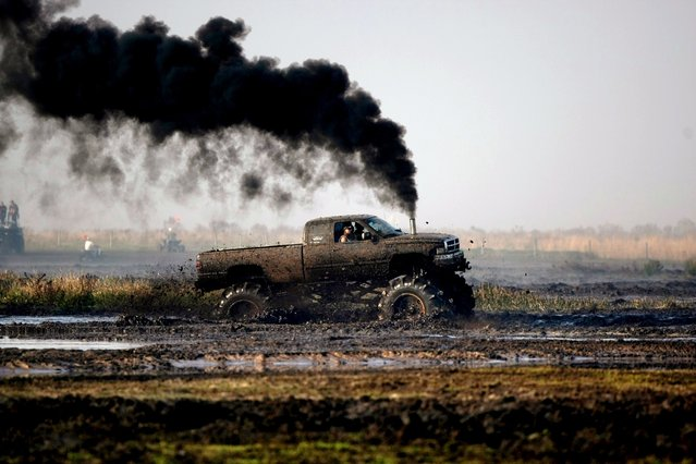 A diesel powered truck billows smoke as it rumbles through the mud bog