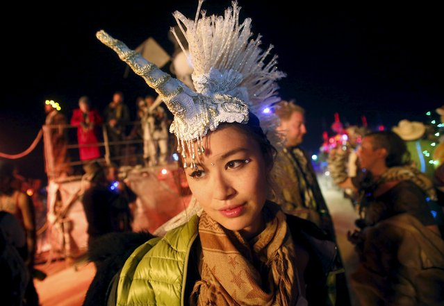 """Sarah Tang wears a unicorn head piece as she dances during the Burning Man 2015 """"Carnival of Mirrors"""" arts and music festival in the Black Rock Desert of Nevada September 5, 2015. (Photo by Jim Urquhart/Reuters)"""