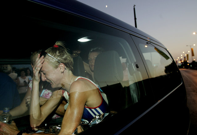 """Britain's Paula Radcliffe cries in a vehicle after retiring from the women's marathon in the Athens 2004 Olympic Games in Greece August 22, 2004. Yannis Behrakis: """"The 2004 Olympics was a very special assignment for me since Athens is my town. The women's marathon was not an event I was initially going to cover. In fact, I had the morning off. On the morning of August 22, a colleague called me frantically to tell me that he had information that the favourite to win the race, the British athlete Paula Radcliffe, had retired about seven kilometres before the end of the 42km race. I took my equipment, jumped on my moped and drove through back roads and alleys – as all roads were blocked by police – to the place about ten blocks north of my home in Athens. (Photo by Yannis Behrakis/Reuters)"""