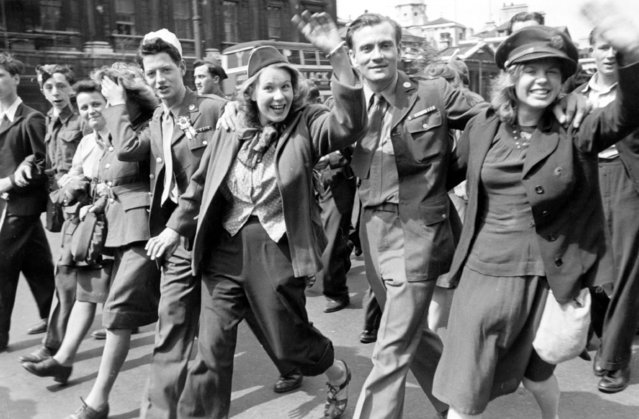 A happy group marches down a London street on VE Day, 8th May 1945. (Photo by Francis Reiss/Picture Post/Hulton Archive/Getty Images)