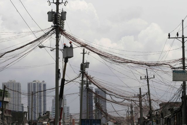 Workers standing in a hydraulic lift examine illegal electrical connections during a routine check on utility poles along a road in a slum area in Manila September 8, 2014. (Photo by Romeo Ranoco/Reuters)
