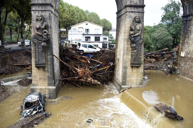 This picture taken on September 18, 2014, in Lamalou-les-Bains, southern France, shows wood pieces and cars stuck under a bridge over the Bitoulet river. Five people died when storms turned a peaceful river that bordered their camping site in southern France into a raging torrent that swept them away, rescue workers said on September 18. (Photo by Pascal Guyot/AFP Photo)
