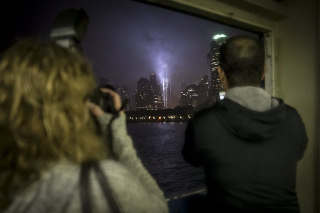 People take photos as they travel on the Staten Island Ferry into lower Manhattan toward the Tribute in Light in New York September 10, 2015. (Photo by Carlo Allegri/Reuters)
