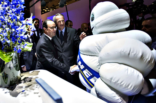 French President Francois Hollande (L) is greeted by President of tire company Michelin, Jean-Dominque Senard (C) and a person dressed in a Michelin-Man costume during an official visit to the Paris Motor Show in Paris on October 03, 2014. The Paris Motor Show, which takes place every two years, runs from October 4 to 19, 2014 with international car makers presenting their latest models and studies. (Photo by Ian Langsdon/AFP Photo)