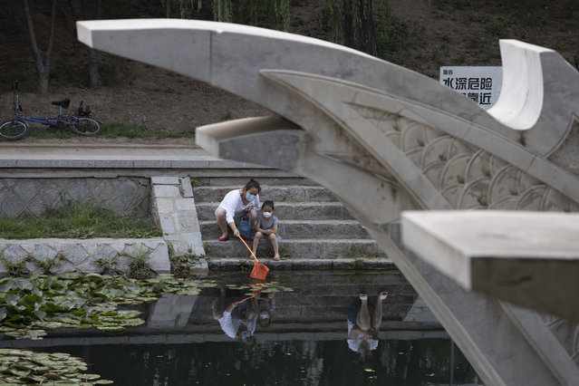 A woman and a child wear masks to curb the spread of the coronavirus as they use a net to look for fish along a canal in Beijing Saturday, June 20, 2020. China's capital recorded a further drop in coronavirus cases amid tightened containment measures. (Photo by Ng Han Guan/AP Photo)