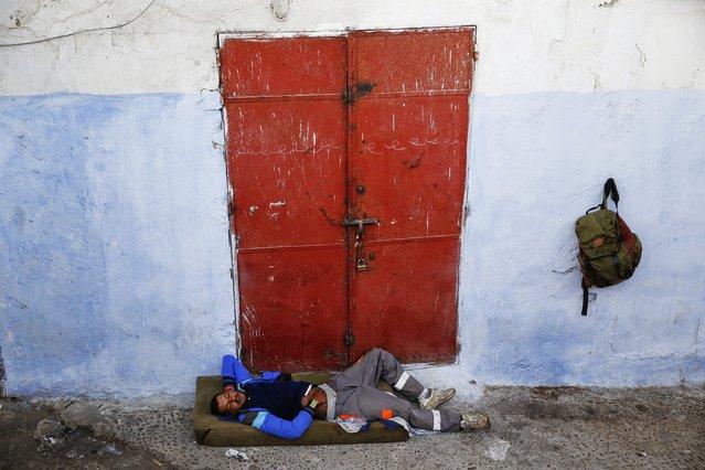 A man sleeps in front of a closed shop in Rabat's Medina September 23, 2014. (Photo by Damir Sagolj/Reuters)
