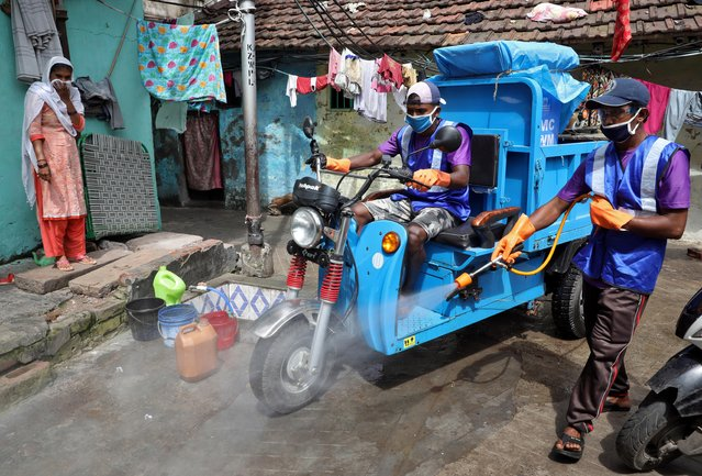 A municipal worker sprays disinfectant to sanitize a slum area to prevent the spread of the coronavirus disease (COVID-19) in Kolkata, India, June 26, 2020. (Photo by Rupak De Chowdhuri/Reuters)