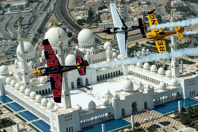 In this handout image provided by Red Bull, Kirby Chambliss (blue plane), Michael Goulian (white) of the United States and Nigel Lamb (yellow) of Great Britain fly over the Sheikh Zayed Mosque during a recon flight prior to the first stop of the Red Bull Air Race World Championship on February 26, 2014 in in Abu Dhabi, United Arab Emirates. (Photo by Joerg Mitter/Red Bull via Getty Images)