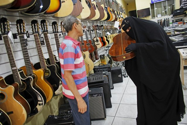 Gisele Marie, a Muslim woman and professional heavy metal musician, checks the sound of a guitar next to a salesman at a shop selling musical instruments in Sao Paulo August 13, 2015. (Photo by Nacho Doce/Reuters)