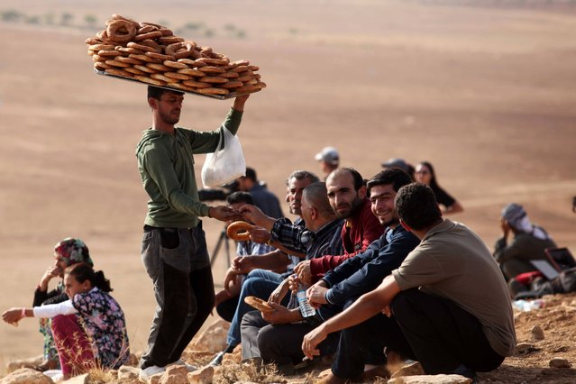 """A vendor sells Turkish traditional bagels called """"simit"""", as people watch the Syrian town of Kobani from near the Mursitpinar border crossing on October 13, 2014 on the Turkish-Syrian border in the southeastern town of Suruc, Sanliurfa province, Turkey. The strategic border town of Kobani has been beseiged by Islamic State militants since mid-September forcing more than 200,000 people to flee into Turkey. (Photo by Gokhan Sahin/Getty Images)"""