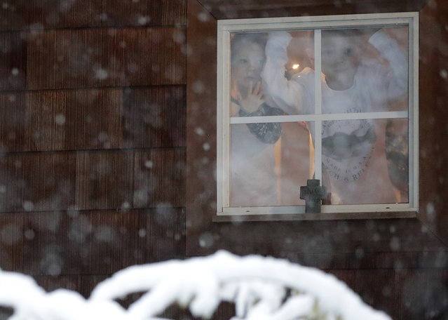 Eden Allen, 3, left, and Josiah Allen, 8, look out their window as a blanket of snow covers the front yard of their home following an early morning snowstorm, Friday, December 8, 2017, in Brandon, Miss. The forecast called for a wintry mix of precipitation across several Deep South states. (Photo by Julio Cortez/AP Photo)