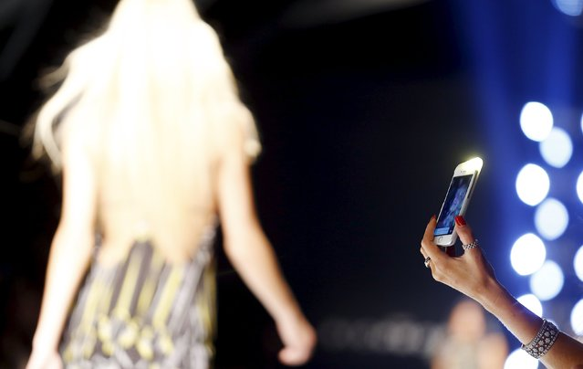 A guest uses a mobile phone during the John Richmond Spring/Summer 2016 collection during Milan Fashion Week in Italy, September 27, 2015. (Photo by Stefano Rellandini/Reuters)