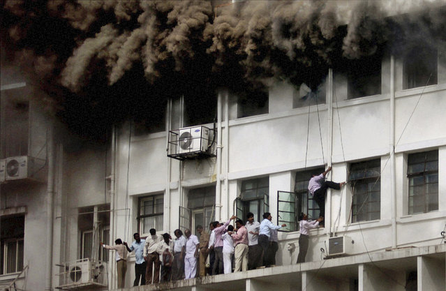 Indian employees are evacuated as smoke billows after the Maharashtra state government caught fire in Mumbai, India, Thursday, June 21, 2012. Hundreds of employees were evacuated Thursday from the seven-story government building as more than two dozen fire engines battled the major fire that raged for more than three hours in India's financial and entertainment capital. (Photo by AP Photo/File)