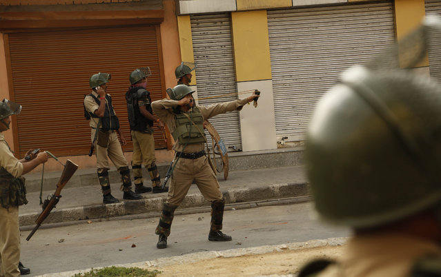 A paramilitary soldier aims his sling shot at Kashmiri protesters in Srinagar, Indian controlled Kashmir Sunday, September 20, 2015.  Kashmiri separatists called for a strike to protest Saturday's killing of a 3-year-old boy and his father in Indian-controlled Kashmir. (Photo by Mukhtar Khan/AP Photo)
