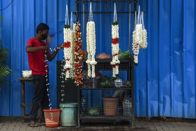 A street vendor prepares flower garlands at a Hindu temple in Colombo on July 2, 2020. (Photo by Ishara S. Kodikara/AFP Photo)