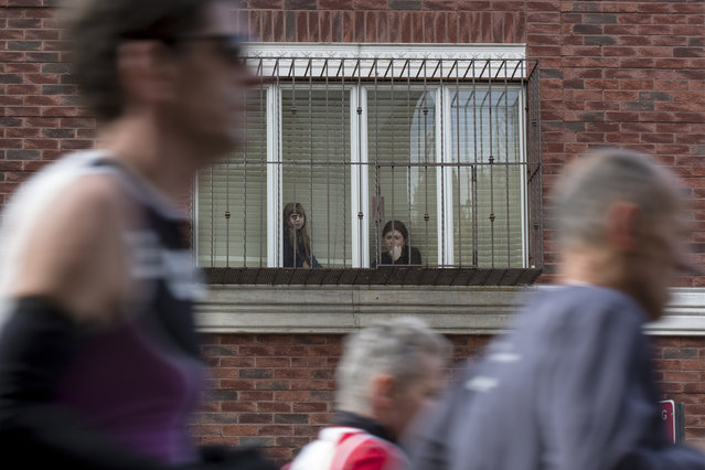 Spectators watch from their window as runners pass, November 2, 2014. (Photo by Brendan McDermid/Reuters)