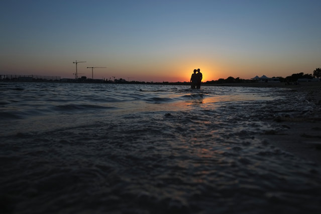 A couple stand in the sea during sunset in coastal resort of Ayia Napa in the eastern Mediterranean island of Cyprus, Saturday, August 22, 2020. Meanwhile, Health Minister Constantinos Ioannou has extended until Jan. 15, 2021, a ban on outdoor festivals, concerts and exhibitions in places without seating where social distancing rules can't be enforced. (Photo by Petros Karadjias/AP Photo)