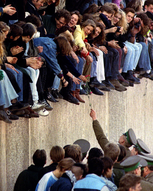 An East Berlin border guard hands a flower back to West Berlin citizens who are sitting atop the Berlin Wall in front of the Brandenburg Gate on November 9, 1989. (Photo by Reuters/Stringer)