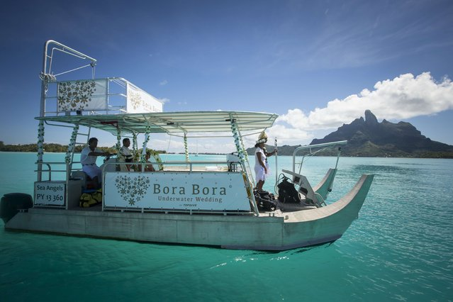 A couple stand aboard a pirogue after their underwater wedding ceremony on October 25, 2014 in Bora-Bora, in French Polynesia. The ceremony lasts twenty minutes and costs around 2700 euros