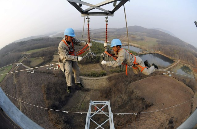 Workers check on electricity pylon situated amid farmlands in Chuzhou, Anhui province, February 5, 2013. A leading think tank of China predicted that China's GDP will grow in 2013 at a rate of 8.4 percent, up by 0.6 percentage points from that of 2012, Xinhua News Agency reported. (Photo by China Daily/Reuters)