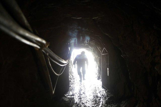 """A mine worker is seen at the entrance of """"The Progreso"""" gold mine near La Paz, November 13, 2014. (Photo by David Mercado/Reuters)"""