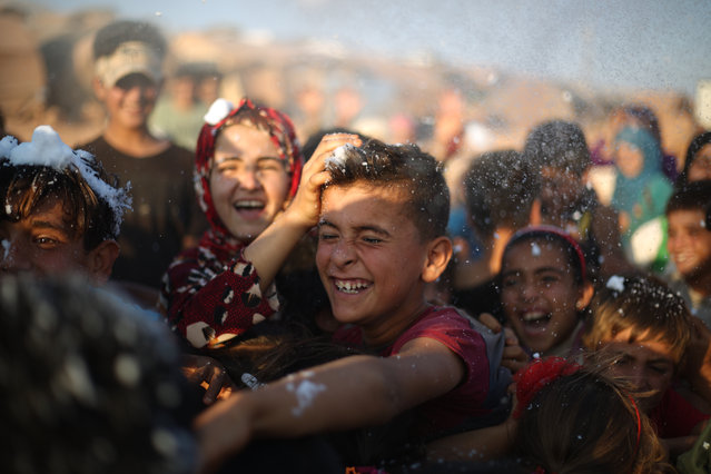A rare moment of joy at the refugee camp as the children receive a visit from an entertainer in Idlib, Syria on August 26, 2020. (Photo by INA Photo Agency/Rex Features/Shutterstock)