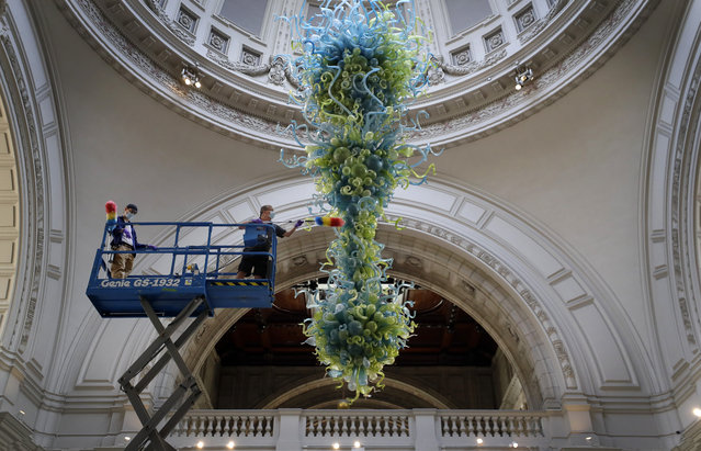 Museum technicians clean one of the V&A's most iconic and largest objects: a 27-foot glass chandelier made up of 1,300 exquisite blue and green glass elements, that hangs in the museum's Grand Entrance at the in London, Tuesday, August 4, 2020. The chandelier is the V&A Rotunda Chandelier by Dale Chihuly, 2001. On loan from Chihuly Studio, Seattle, Washington, USA. The museum will reopen to the public on Thursday Aug.6. (Photo by Kirsty Wigglesworth/AP Photo)