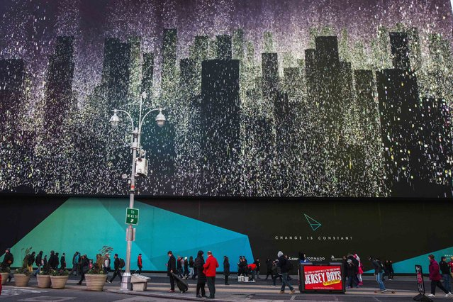 Pedestrians walk underneath a giant new advertising screen in Times Square, New York, November 19, 2014. (Photo by Carlo Allegri/Reuters)