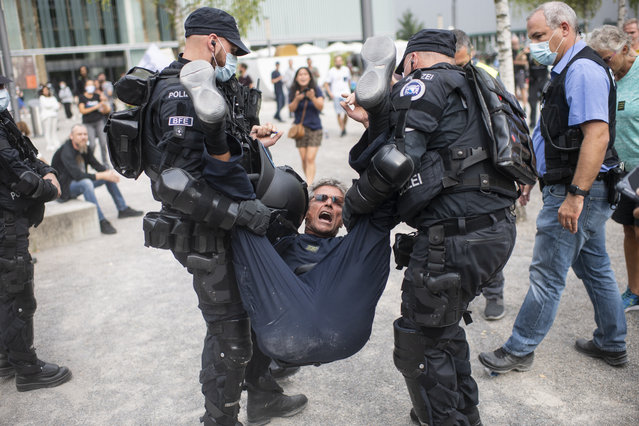 Policemen arrest a demonstrator who attends a protest against the Swiss government's measures to slow down the spread of the coronavirus disease (COVID-19), at the Turbinenplatz in Zurich, Switzerland, Saturday, September 19, 2020. (Photo by Ennio Leanza/Keystone via AP)