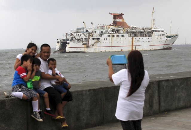 A family takes photos in front of a ferry boat that ran aground due to strong waves brought by Typhoon Koppu near the breakwater of Manila bay on October 19, 2015. Typhoon Koppu swept across the northern Philippines killing at least nine people as trees, power lines and walls were toppled and flood waters spread far from riverbeds, but tens of thousands of people were evacuated in time. (Photo by Romeo Ranoco/Reuters)