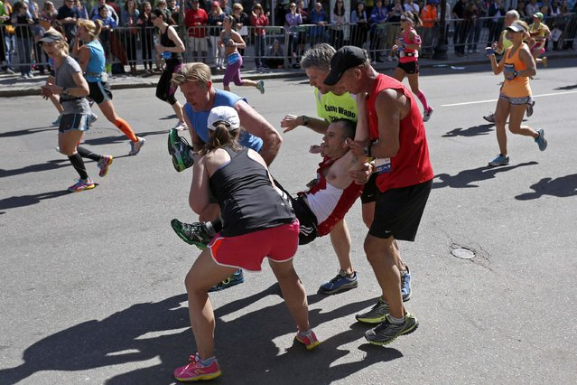 Four runners carry Adam Hurst down Boylston Street after his legs locked up during the 118th running of the Boston Marathon in Boston, Massachusetts in this April 21, 2014 file photo. I was positioned near the Forum restaurant in case anything significant happened at the time and place of last year's second bomb attack. (Photo and caption by Dominick Reuter/Reuters)