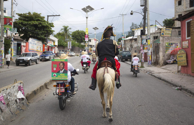 In this October 17, 2015 photo, a man dressed as independence hero Jean Jacques Dessalines rides a horse alongside fellow campaigners on motorcycles as they promote presidential candidate Moise Jean Charles, of the Platform Pitit Dessalines political party, in Port-au-Prince, Haiti. (Photo by Dieu Nalio Chery/AP Photo)