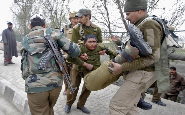 Indian paramilitary soldiers carry their injured colleague to a hospital during the gunfight in Srinagar, on March 13, 2013. (Photo by Danish Ismail/Reuters)