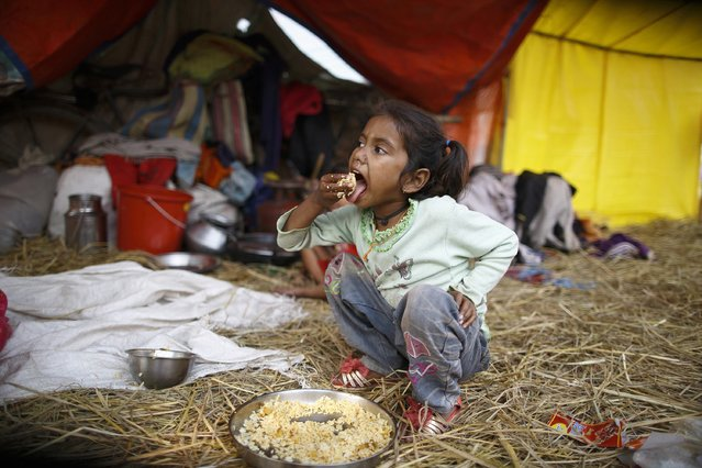 "A girl eats her lunch inside a tent during the ""Gadhimai Mela"" festival held in Bariyapur November 29, 2014. (Photo by Navesh Chitrakar/Reuters)"