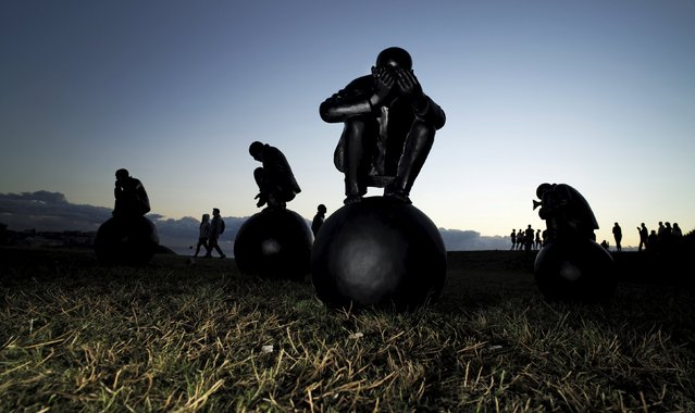 "A painted bronze by Chinese artist Wang Shugang titled ""Man on Ball"" is pictured among visitors during the 19th annual Sculpture by the Sea exhibition in Sydney, Australia October 24, 2015. (Photo by Jason Reed/Reuters)"
