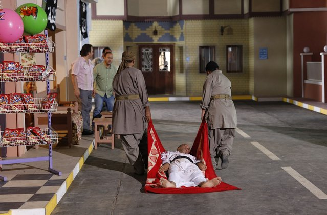 """Actors are seen during the filming of the television series, the title of which is loosely translated as """"State of Myths"""", on set in Baghdad, in this October 10, 2014 file photo. (Photo by Thaier Al-Sudani/Reuters)"""