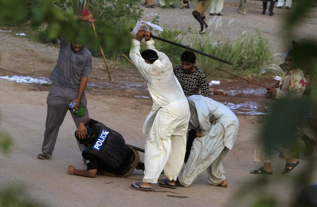 Anti-government protesters beat a riot policeman after clashes during the Revolution March in Islamabad, in this September 1, 2014 file photo. (Photo by Faisal Mahmood/Reuters)