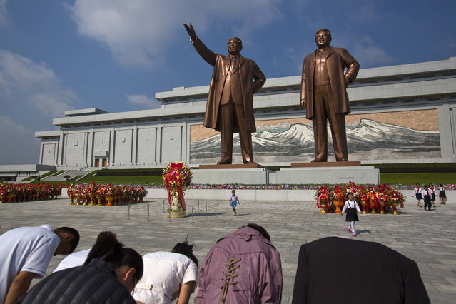 North Koreans bow in front of bronze statues of the late leaders Kim Il Sung, left, and Kim Jong Il at the Mansu Hill area of Pyongyang on Sunday September 9, 2012, to celebrate the country's National Day. (Photo by David Guttenfelder/AP Photo)