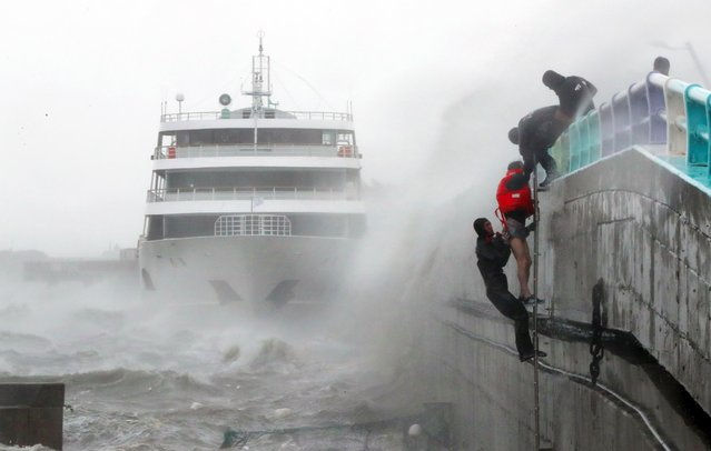 South Korean coast guards try to rescue crew members of a stranded passenger ship in the aftermath of typhoon Chaba in the southern city of Yeosu on October 5, 2016. (Photo by AFP Photo/Yonhap)