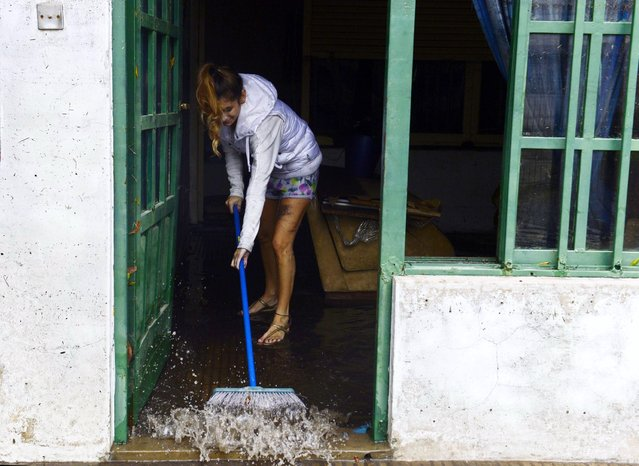 A woman starts cleaning her house as the water subsides in La Plata, located 63 km south of Buenos Aires, on April 3, 2013 after a powerful storm that earlier pummeled in the Argentine capital slammed here overnight Tuesday to Wednesday. At least 25 people died in flooding in La Plata as a record 40 cm of rain fell in a two hour period, knocking out phone lines and leaving people in the dark. The deaths raised to 33 the number of people killed this week following record heavy rain in Argentina. (Photo by Daniel Garcia/AFP Photo)