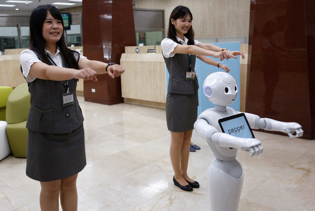 """SoftBank's robot """"Pepper"""" performs with employees at First Bank branch in Taipei, Taiwan October 6, 2016. (Photo by Tyrone Siu/Reuters)"""