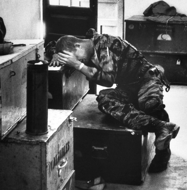 In a supply shack, hands covering his face, an exhausted, worn James Farley gives way to grief. (Photo by Larry Burrows/Time & Life Pictures)
