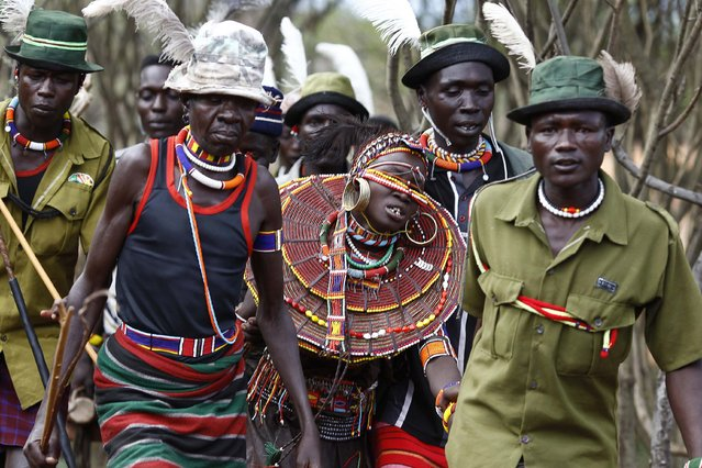 Pokot men hold onto a a girl as they lead her to be married to a member of their community after the group came to take her from her family home, about 80 km (50 miles) from the town of Marigat in Baringo County December 7, 2014. (Photo by Siegfried Modola/Reuters)